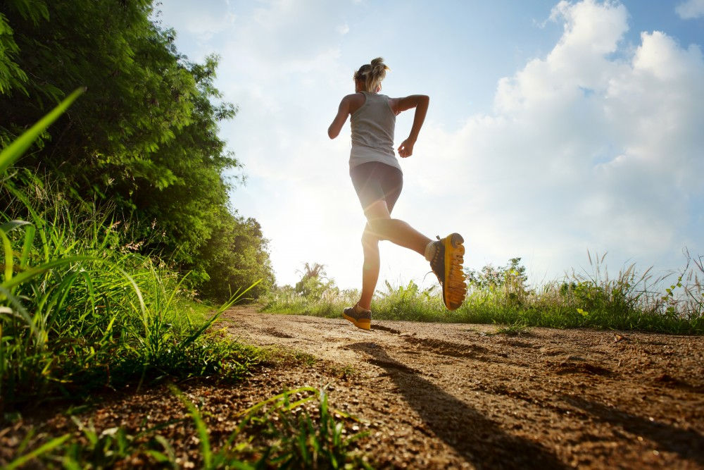 Woman running up a dirt hill with the sun shining in the background